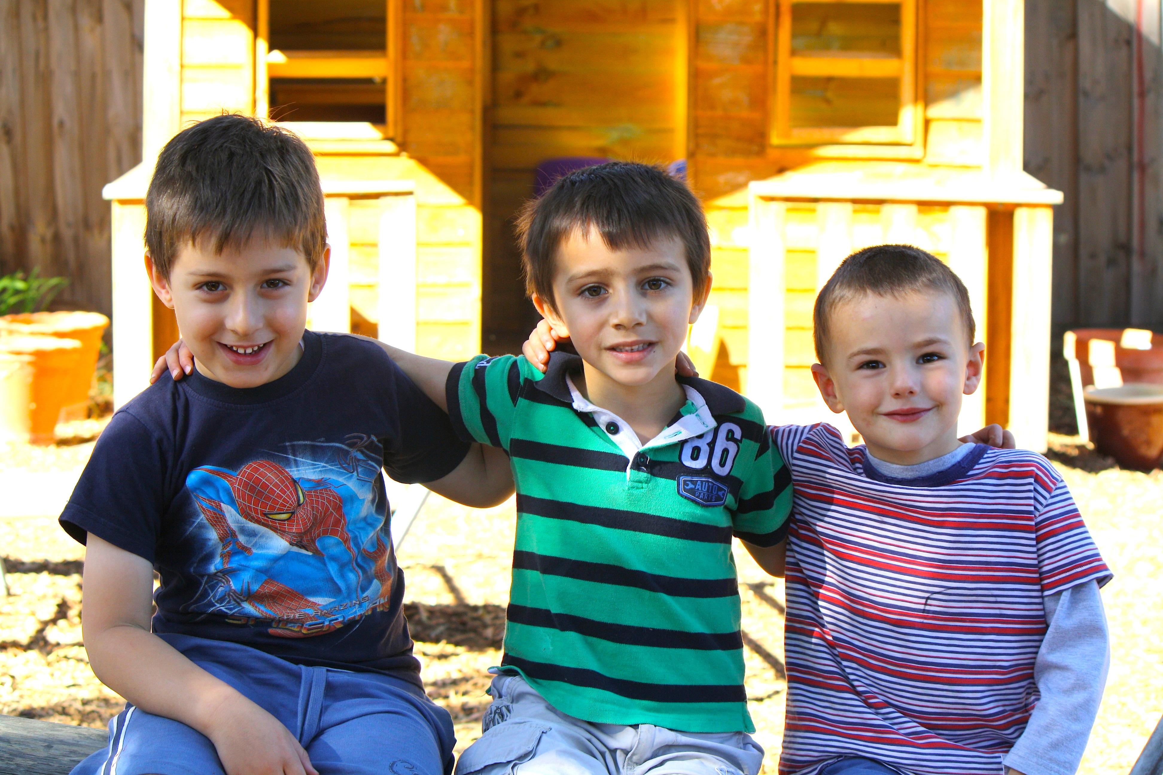 Three boys sitting in a row
